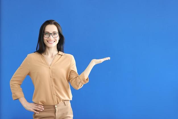 Женщина в очках показывает жест рукой на синем фоне