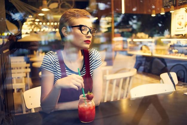 Женщина в очках сидит за столиком в кафе с коктейльным напитком в свободное время
