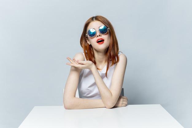 白いテーブルに座っている眼鏡をかけた女性の感情は魅力的な外観を魅了します