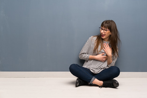 Woman with glasses sitting on the floor smiling a lot