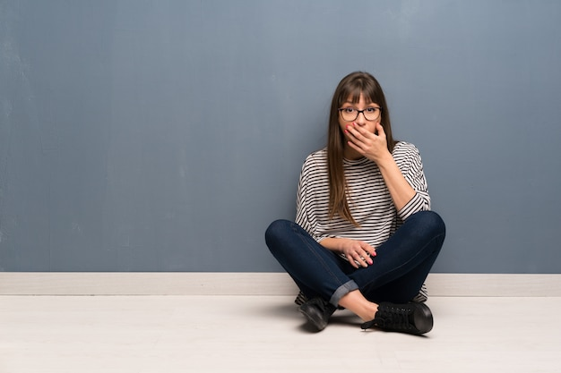 Woman with glasses sitting on the floor surprised and shocked while looking right