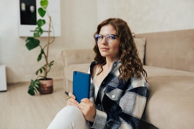 ソファの近くの床に座って、メモ帳を持っている眼鏡をかけた女性