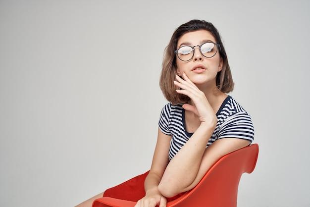 赤い椅子に座っている眼鏡をかけた女性は、ビューの魅力をトリミングしました