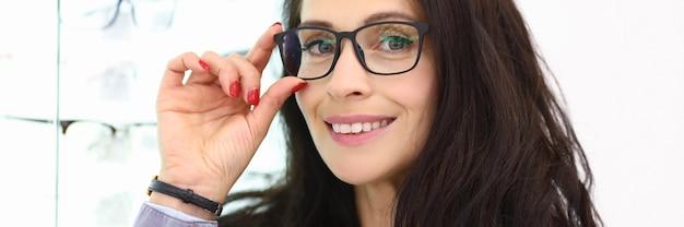 眼鏡をかけた女性は、光学系のショーウィンドウの隣に立っています。レンズとメガネのコンセプトの販売のためのショップ