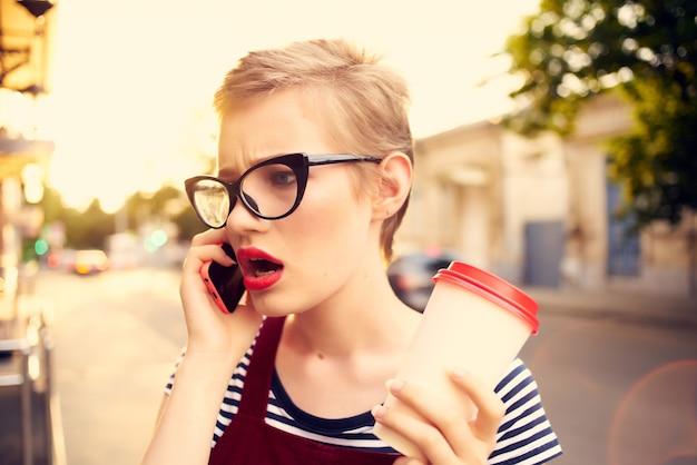 通りで電話で話している眼鏡をかけた女性一杯のコーヒー