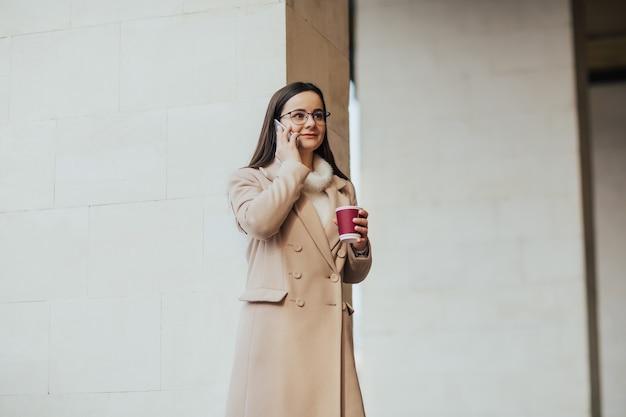 スマートフォンで話し、コーヒーを飲む眼鏡をかけた女性