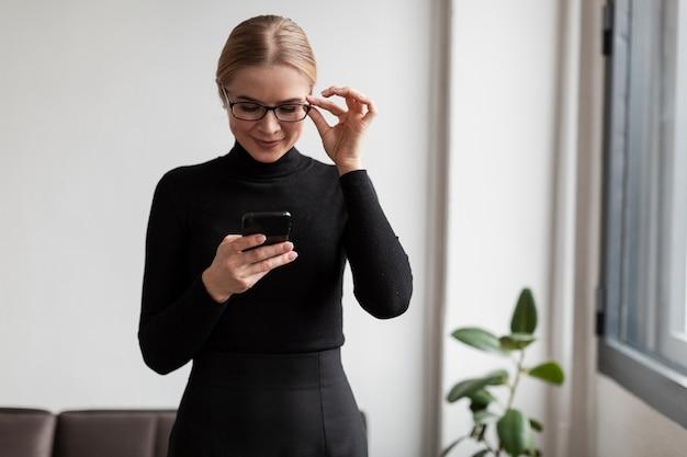 Donna con gli occhiali utilizzando mobile