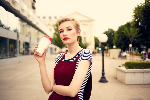 A woman with glasses walks around the city a glass with a drink leisure communication. high quality photo
