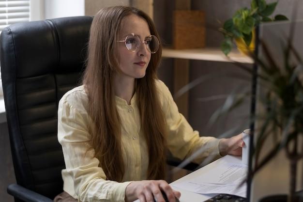 眼鏡をかけた女性は、ドキュメントを使用してpcで作業します。オフィスのビジネスウーマンは、仕事上の問題を解決します。