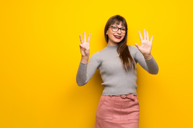 Woman with glasses over yellow wall counting eight with fingers