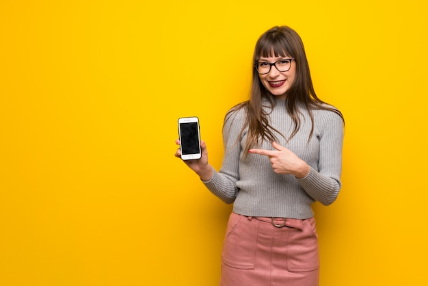 Woman with glasses over yellow wall happy and pointing the mobile