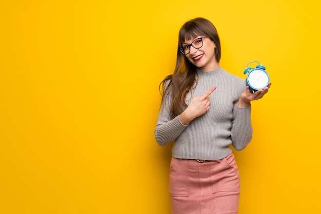 Woman with glasses over yellow wall holding vintage alarm clock