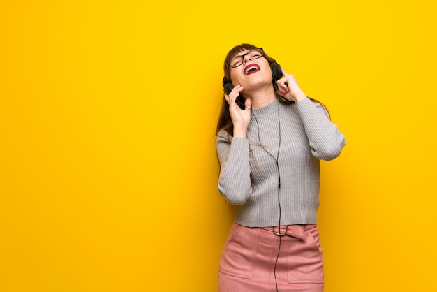 Woman with glasses over yellow wall listening to music with headphones