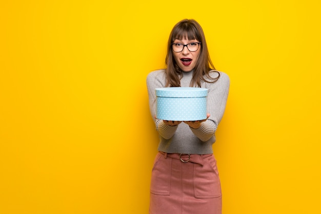 Woman with glasses over yellow wall surprised because has been given a gift