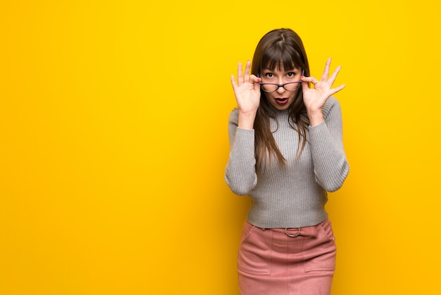 Woman with glasses over yellow wall with glasses and surprised