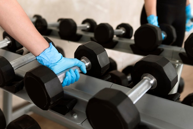 Woman with glove holding weight at the gym