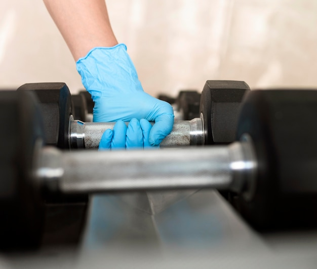 Woman with glove holding weight while at the gym