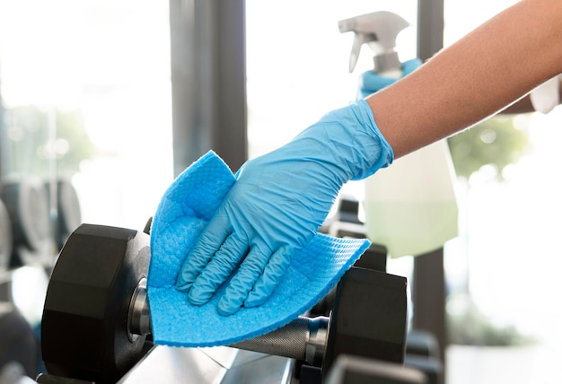Donna con guanti che disinfettano i pesi in palestra
