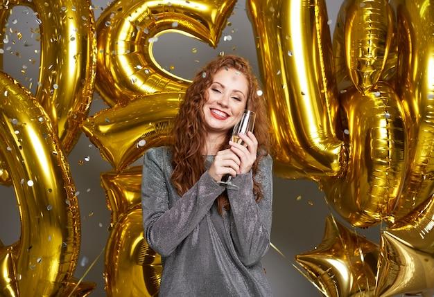 紙吹雪のシャワーの下で金色の風船とシャンパンを持つ女性