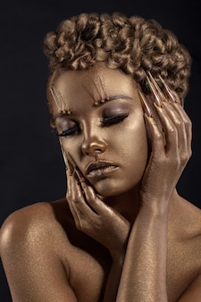 Woman with golden makeup. shiny skin effect jewelry.