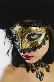 Woman with a golden venetian mask and a black hat on a white background