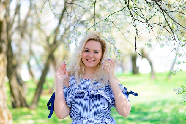Woman with gorgeous smile having fun in blooming garden. female in blue dress on natural background.