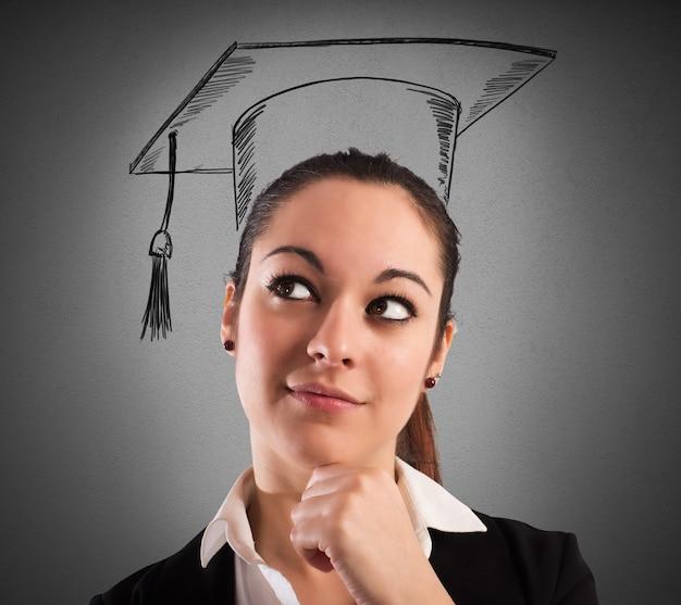 Женщина с нарисованной выпускной шляпой и задумчивым выражением лица