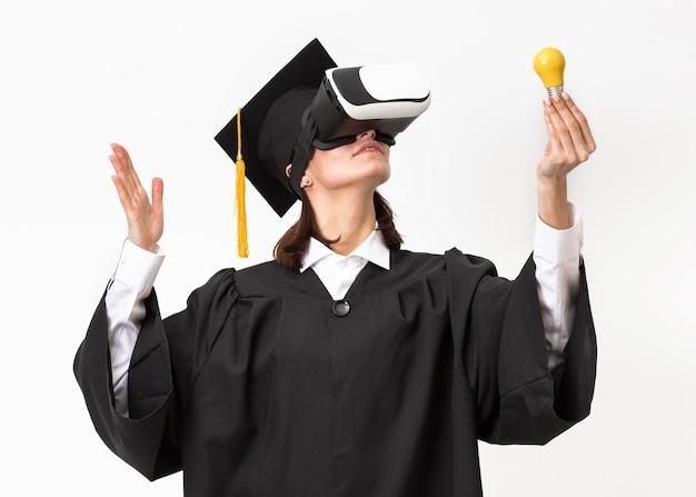 バーチャルリアリティヘッドセットを身に着けている卒業ローブとキャップを持つ女性
