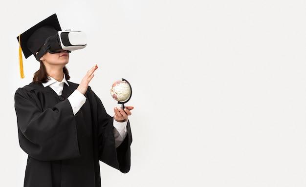 Donna con veste di laurea e berretto che indossa le cuffie da realtà virtuale
