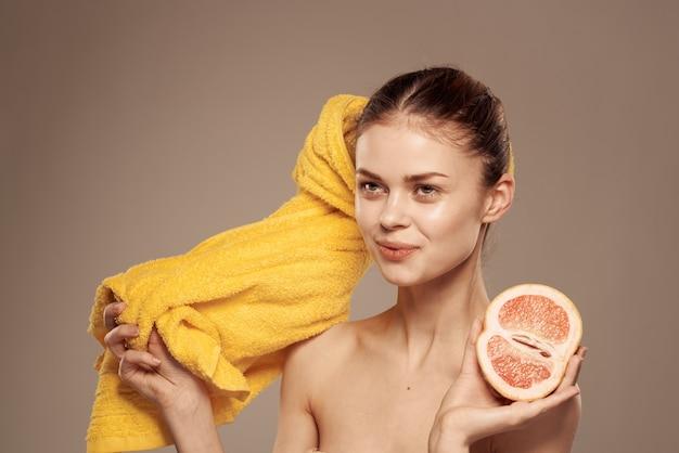 手にグレープフルーツを持った女性きれいな肌素肩スパヘルストリートメント
