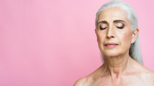 Woman with gray hair on pink background
