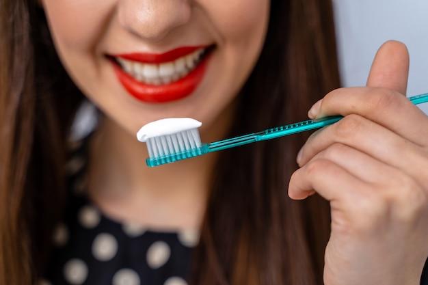 Женщина с большими зубами, держа зубную щетку перед камерой. размытый фон.