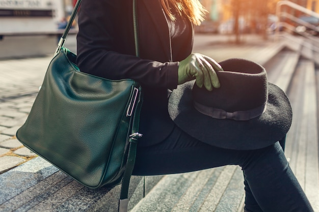 Woman with gree handbag wearing gloves and holding black hat outdoors