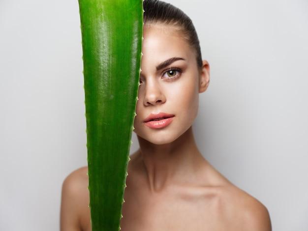 目の前に緑のアロエの葉を持つ女性きれいな肌の美容自然な外観