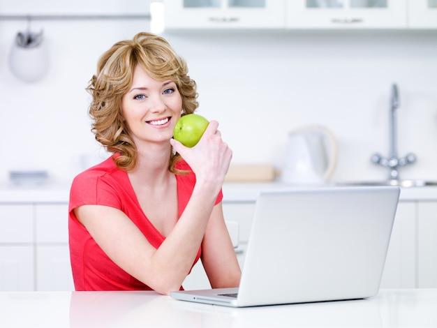 녹색 사과와 부엌에 앉아 노트북을 가진 여자