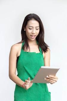 緑のエプロンを持つ女性はソーシャルメディアのタブレットを使用します