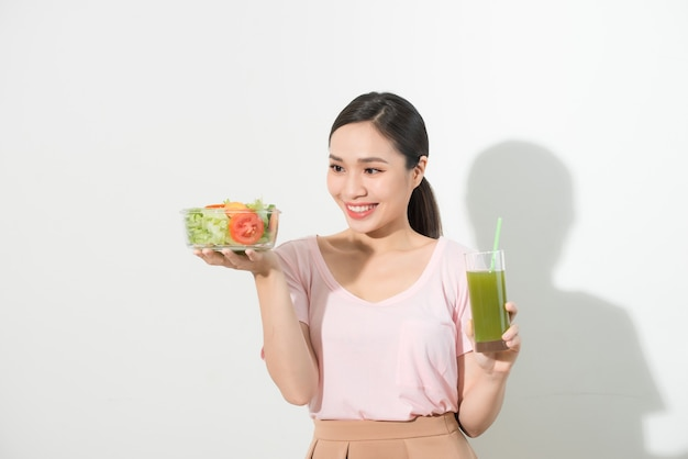 緑のデトックススムージー、分離されたガラスのボウルにサラダを持つ女性。適切な栄養、ベジタリアン料理、健康的なライフスタイル、ダイエットのコンセプト。スペースをコピーする領域