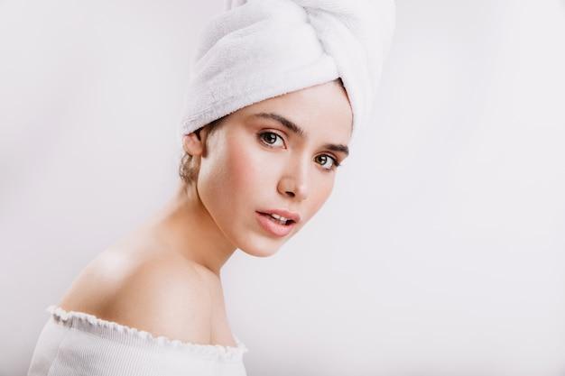 Женщина с зелеными глазами. здоровая кожа дама позирует в полотенце после душа.