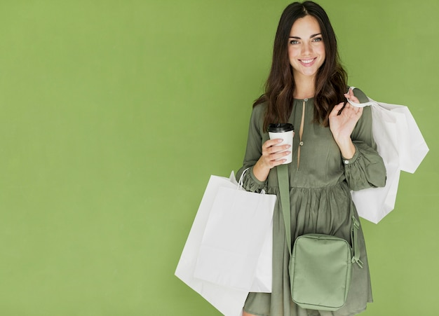 Woman with green handbag and coffee on green background