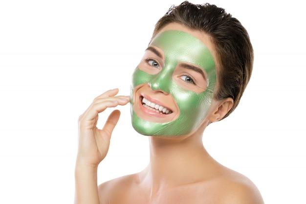 그녀의 얼굴에 녹색 필 오프 마스크를 가진 여자