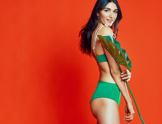 緑の水着のヤシの葉の熱帯地方の赤い背景を持つ女性