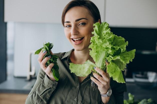 台所で緑の野菜を持つ女性