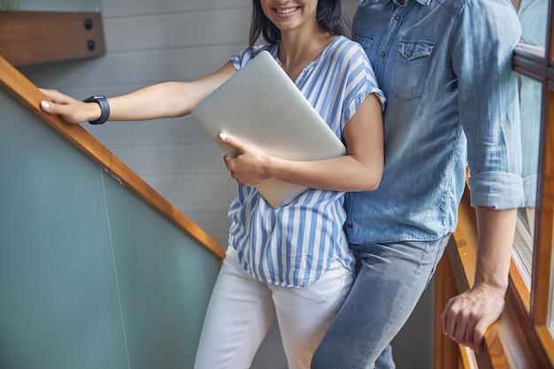 현대 집에서 그녀의 남자 친구 앞에 서있는 동안 손에 회색 노트북을 가진 여자