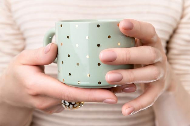 컵을 들고 누드 베이지 핑크 네일 디자인으로 손질 된 손으로 여자. 매니큐어, 패션 및 뷰티 살롱 개념