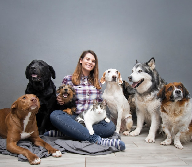 Woman with group of mixed breed dogs