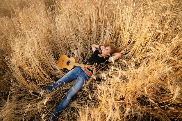 Woman with a guitar lying in the wheat field