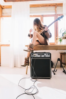 Woman with guitar sitting on table