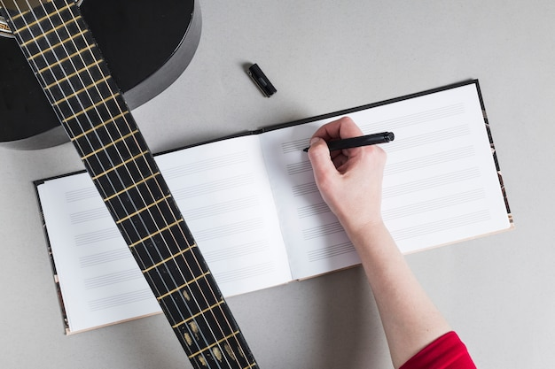 Woman with guitar writing down notes