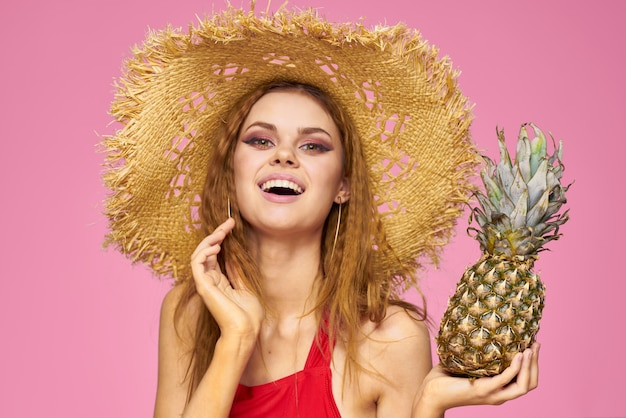 Woman with a gun in hands of a straw hat bright makeup exotic fruits summer pink.