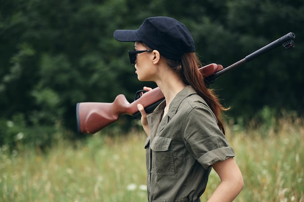 Woman with a gun outdoors in the forest and green grass trees